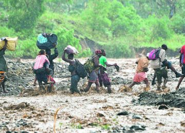 Haitian people cross the river La Digue in Petit Goave where the bridge collapsed during the rains of the Hurricane Matthew, southwest of Port-au-Prince, October 5, 2016. Haiti and the eastern tip of Cuba -- blasted by Matthew on October 4, 2016 -- began the messy and probably grim task of assessing the storm's toll. Matthew hit them as a Category Four hurricane but has since been downgraded to three, on a scale of five, by the US National Hurricane Center. / AFP PHOTO / HECTOR RETAMAL