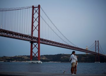 A couple takes a picture near the 25 April Bridge in Lisbon, Portugal August 22, 2016. Picture taken August 22, 2016. REUTERS/Rafael Marchante