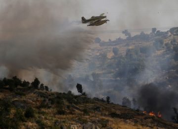 An aircraft drops water over a forest fire near Lagoaca, Portugal September 8, 2016. REUTERS/Miguel Vidal
